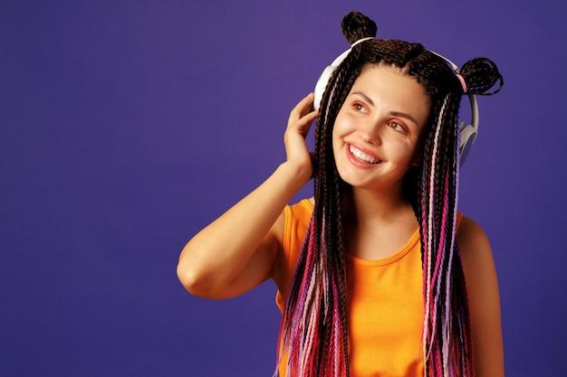 Jovem mulher caucasiana com trancinhas africanas ouvindo música com fones de ouvido