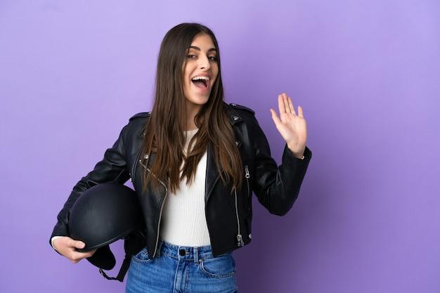 Jovem mulher caucasiana com um capacete de motociclista isolada em um fundo roxo, saudando com a mão com uma expressão feliz