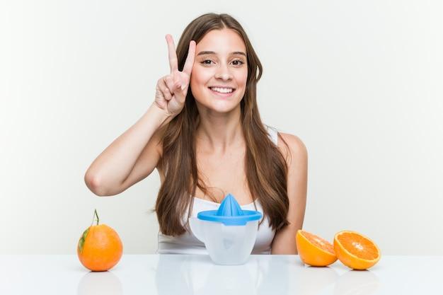 Jovem mulher caucasiana com um espremedor de laranja mostrando sinal de vitória e sorrindo amplamente.