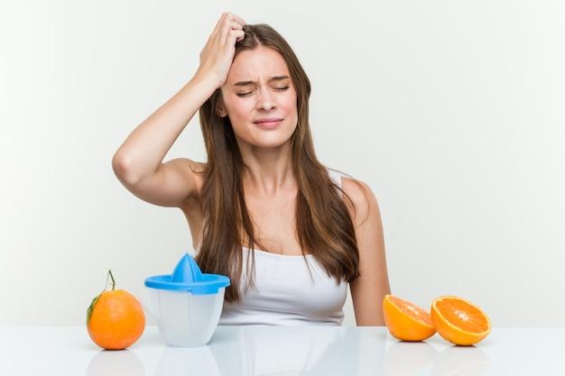 Jovem mulher caucasiana com um espremedor de laranja sendo chocado, ela se lembrou de uma reunião importante.