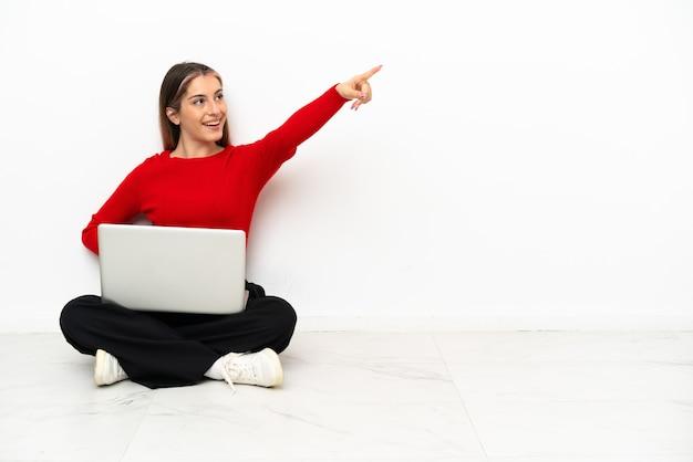 Jovem mulher caucasiana com um laptop sentada no chão apontando para longe
