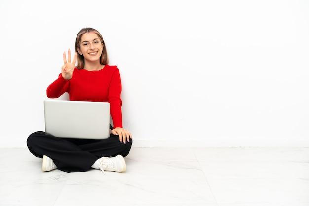 Jovem mulher caucasiana com um laptop sentada no chão feliz e contando três com os dedos