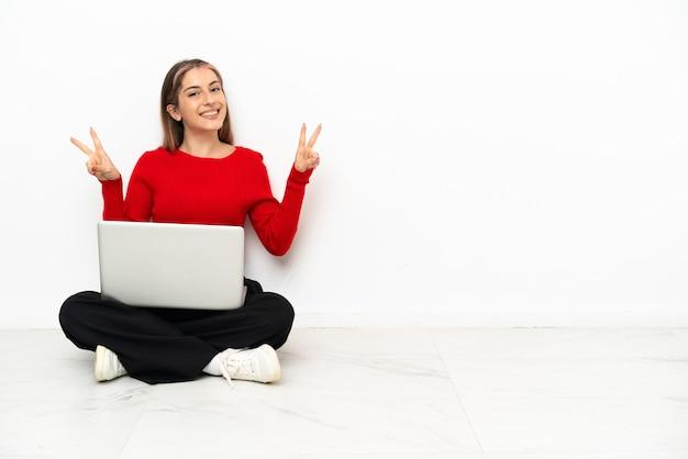 Jovem mulher caucasiana com um laptop sentado no chão, mostrando o sinal da vitória com as duas mãos