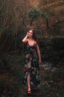 Jovem mulher caucasiana com um vestido colorido no meio da floresta ao lado de um pequeno rio