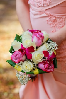 Jovem mulher caucasiana com vestido de renda rosa segura um buquê com flores e rosas cor de rosa do jardim nas mãos