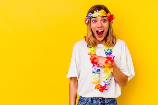 Jovem mulher caucasiana comemorando festa havaiana isolada na parede amarela apontando para o lado