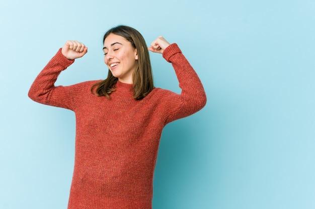 Jovem mulher caucasiana, comemorando um dia especial, pula e levanta os braços com energia.