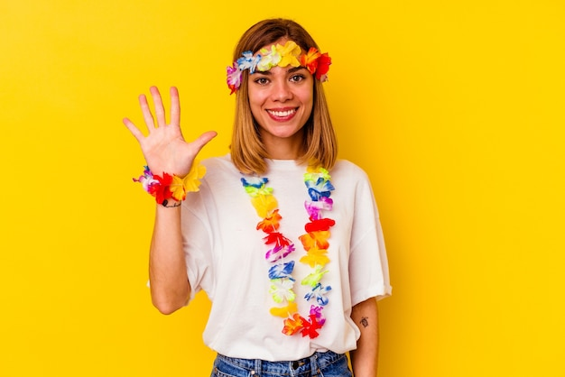 Jovem mulher caucasiana, comemorando uma festa havaiana, sorrindo alegre mostrando o número cinco com os dedos.