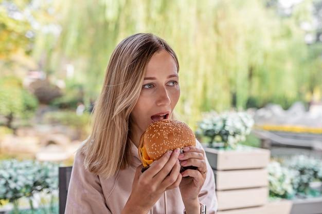 Jovem mulher caucasiana comendo cheeseburguer em uma cafeteria ao ar livre no verão.