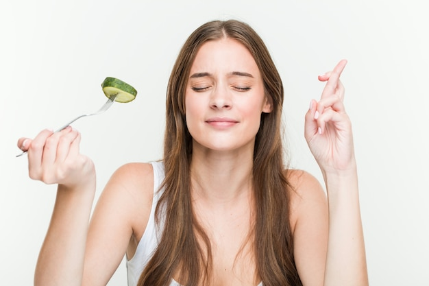Jovem mulher caucasiana comendo pepino cruzando os dedos por ter sorte