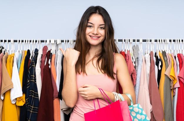 Jovem mulher caucasiana, comprando roupas em uma loja, apontando para o lado para apresentar um produto