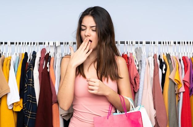 Jovem mulher caucasiana, comprar algumas roupas em uma loja bocejando