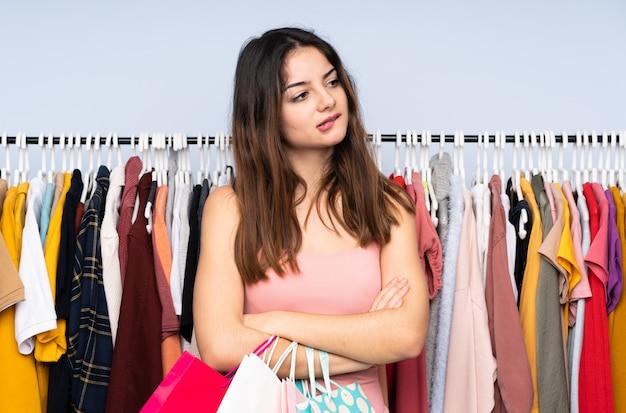 Jovem mulher caucasiana, comprar algumas roupas em uma loja com confundir a expressão do rosto