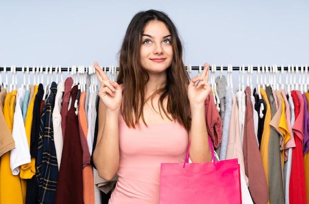 Jovem mulher caucasiana, comprar algumas roupas em uma loja com os dedos cruzando e desejando o melhor
