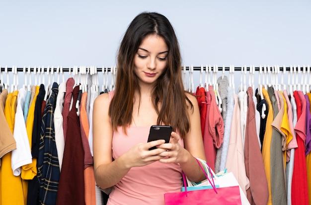 Jovem mulher caucasiana, comprar algumas roupas em uma loja, enviando uma mensagem com o celular