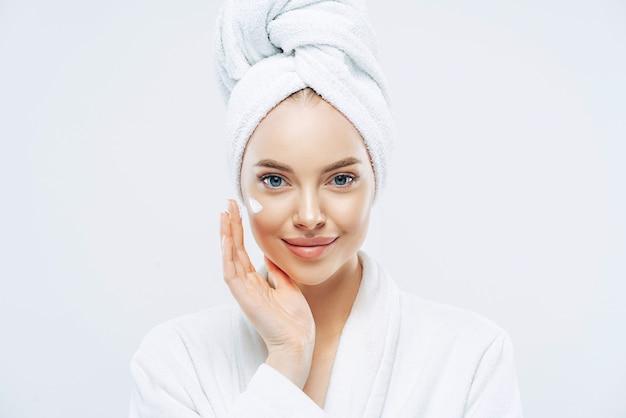 Jovem mulher caucasiana confiante aplicando creme facial e gostando de produto cosmético