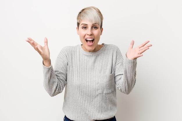 Jovem mulher caucasiana curvilínea isolada no branco, recebendo uma surpresa agradável, animado e levantando as mãos.