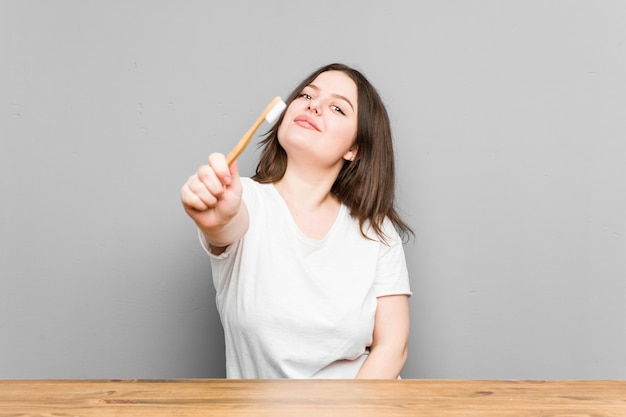 Jovem mulher caucasiana curvilínea, limpando os dentes com uma escova de dentes isolada em uma parede cinza