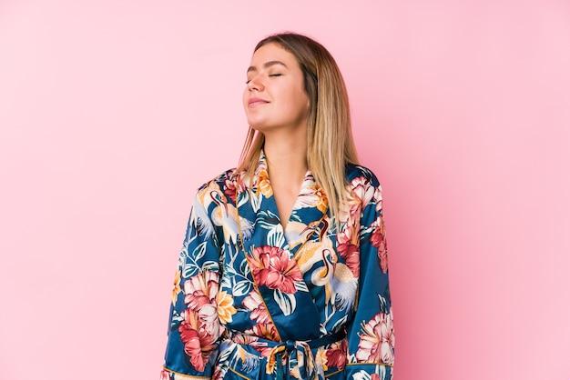 Jovem mulher caucasiana de pijama e sonhando em alcançar objetivos e propósitos