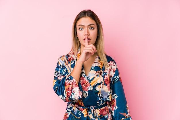 Jovem mulher caucasiana de pijama, mantendo um segredo ou pedindo silêncio.