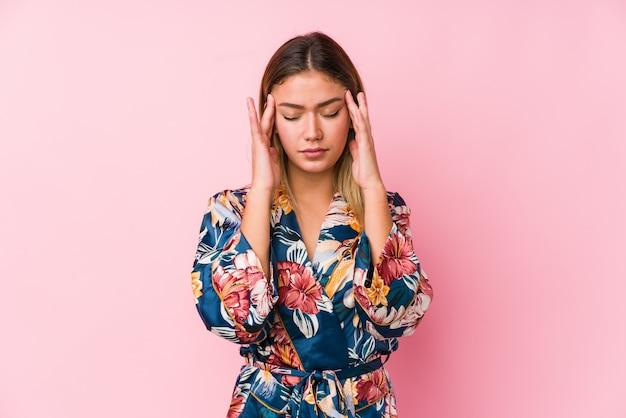 Jovem mulher caucasiana de pijama tocando os templos e tendo dor de cabeça.
