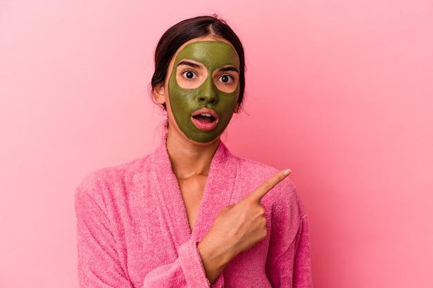 Jovem mulher caucasiana de roupão e máscara facial isolada em um fundo rosa apontando para o lado