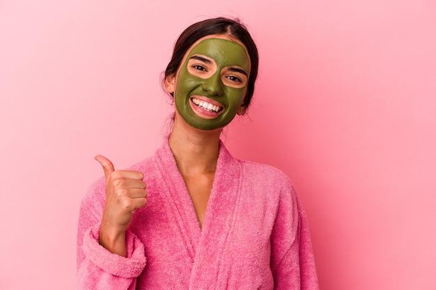 Jovem mulher caucasiana de roupão e máscara facial isolada em um fundo rosa, sorrindo e levantando o polegar