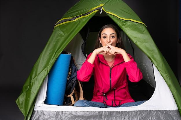 Jovem mulher caucasiana dentro de uma barraca de acampamento verde
