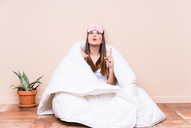 Jovem mulher caucasiana, descansando com uma colcha apontando para cima com a boca aberta.