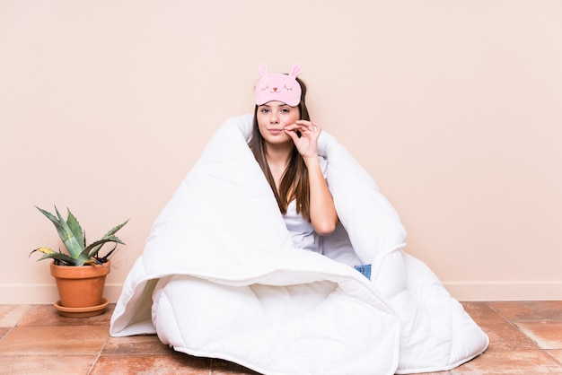 Jovem mulher caucasiana, descansando com uma colcha com os dedos nos lábios, mantendo um segredo.