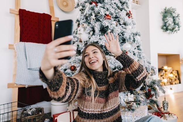 Jovem mulher caucasiana deseja feliz natal por videochamada usando telefone celular nas férias em casa no sofá.