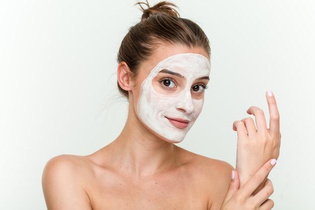 Jovem mulher caucasiana, desfrutando de um tratamento de pele