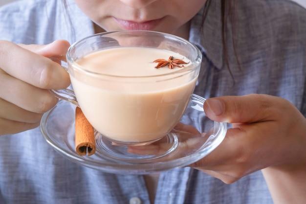 Jovem mulher caucasiana, desfrutando de uma xícara de chá masala chai