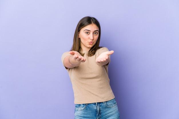 Jovem mulher caucasiana, dobrando os lábios e segurando as palmas das mãos para enviar beijo no ar.