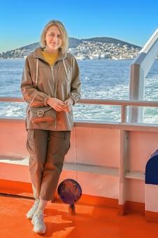 Jovem mulher caucasiana em barco de recreio ao largo da costa de istambul, distrito de adalar, turquia, no mar de mármara.