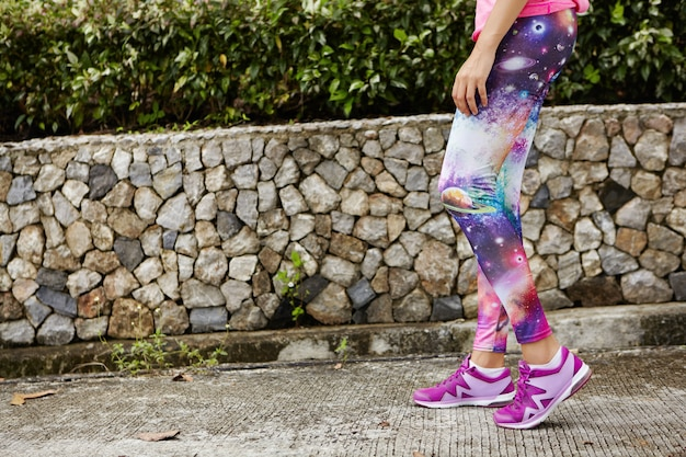 Jovem mulher caucasiana em forma de corredor com roupas esportivas elegantes e tênis roxos, malhando em um dia ensolarado no parque da cidade