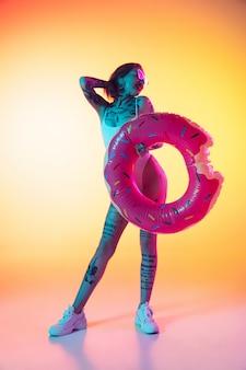Jovem mulher caucasiana em maiô com donut de borracha em fundo gradiente amarelo em luz de néon. linda modelo com tatuagens. emoções humanas, vendas, conceito de anúncio. resort e férias, verão.