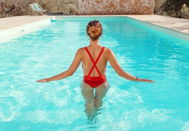 Jovem mulher caucasiana em maiô vermelho relaxando em uma piscina