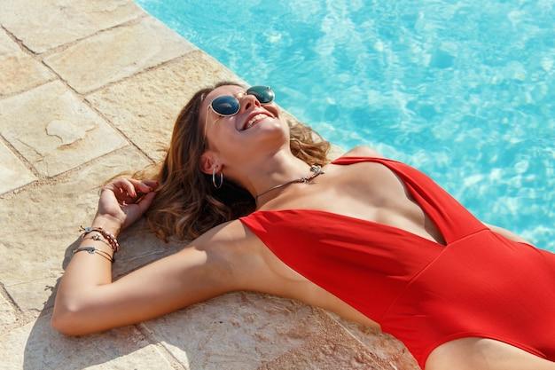 Jovem mulher caucasiana em maiô vermelho relaxando perto de uma piscina