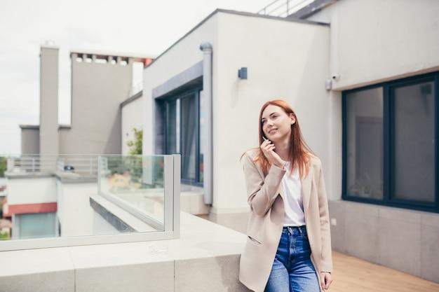 Jovem mulher caucasiana em pé no terraço fumando maconha