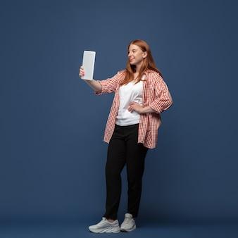 Jovem mulher caucasiana em roupa casual com tablet