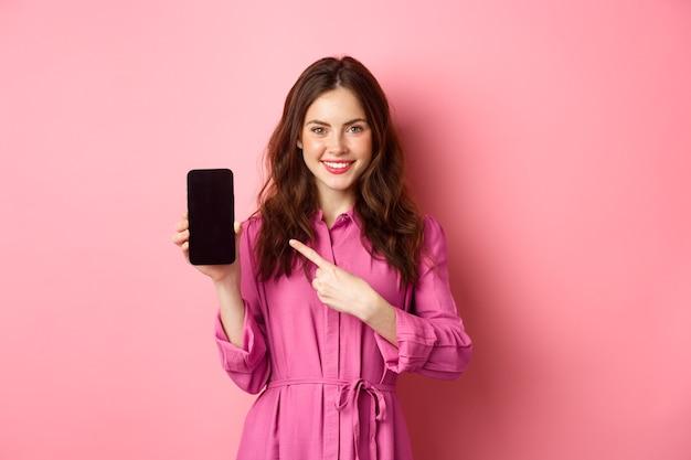 Jovem mulher caucasiana em um vestido elegante, apontando o dedo para a tela do smartphone e sorrindo, mostrando a oferta promocional online, parede rosa.