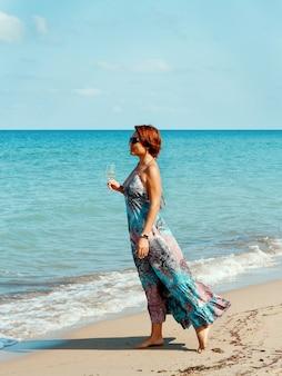 Jovem mulher caucasiana em um vestido longo com uma taça de vinho na mão caminhando na praia