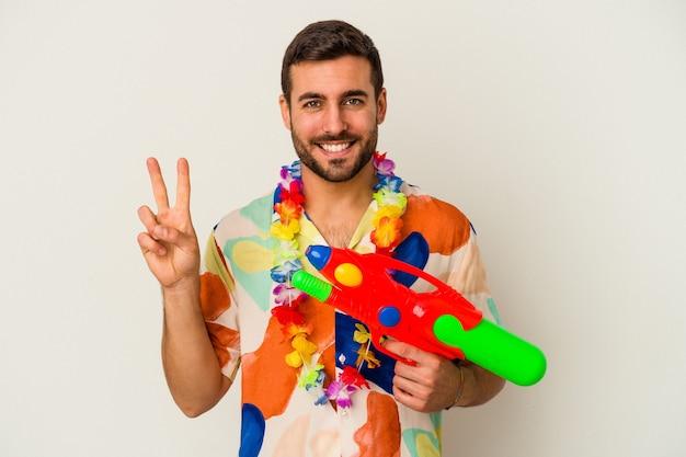 Jovem mulher caucasiana em uma festa havaiana segurando uma pistola de água isolada na parede branca, mostrando o número dois com os dedos.