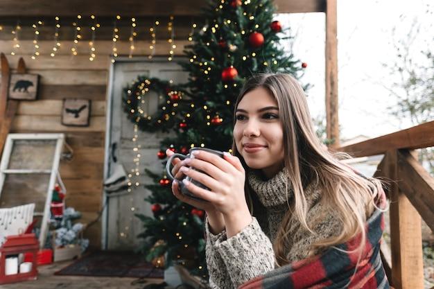 Jovem mulher caucasiana em uma manta está bebendo uma bebida quente na varanda com a árvore de natal e enfeites.