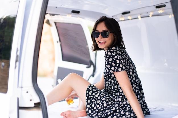 Jovem mulher caucasiana em uma van de camping ao ar livre