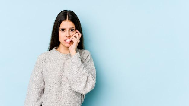 Jovem mulher caucasiana em unhas cortantes de parede azul, nervoso e muito ansioso.