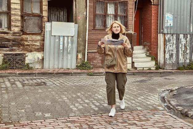 Jovem mulher caucasiana em viagem para istambul é guiada pela área no mapa de papel.