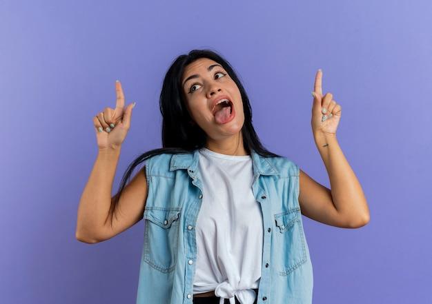 Jovem mulher caucasiana engraçada tira a língua de fora e aponta para cima com as duas mãos isoladas no fundo roxo com espaço de cópia