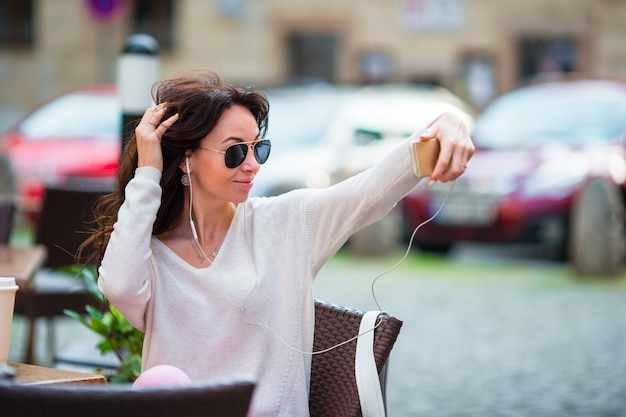 Jovem mulher caucasiana, enviando mensagem e tendo auto-retrato no café ao ar livre